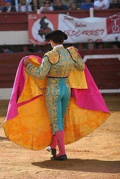 El matador uso la capa con muchos colores por practica . En la arena el matador uso la capa rojo. Los torros corren Despues la cosa que rapidamente.