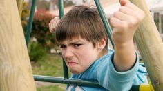 Wütender, trauriger Junge auf Spielplatz hält verärgert Faust in Kamera