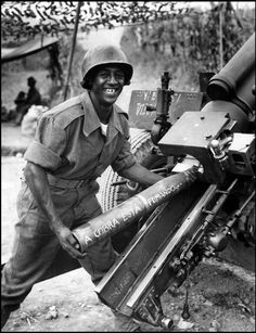 Brаzilian artillery crewman in Italy during WWII, with a artillery shell written The Snake is Smoking.