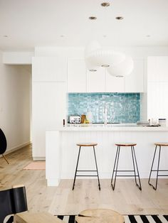 The white kitchen of this beachside residence is brought to life by a sky blue backsplash and light wood accents.