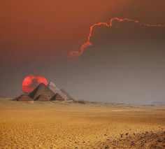 A gorgeous, swollen red sun sets behind the pyramids of the Giza Plateau.