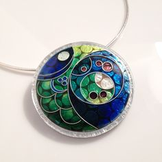 Large cloisonne enamel set in an innovative lasercut lucite and silver setting.