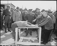 General Dwight D. Eisenhower watches as prisoners demonstrate how they were tortured at the concentration camp at Gotha. Photo April 12, 1945.
