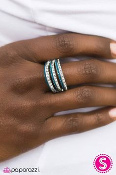 Paparazziaccessories.com/58750  The Band Leader - Blue  Three beveled rows of silver arc elegantly across the finger. One side of each silver band is glazed in the rich shade of Deep Caribbean, while the other side of each band is dipped in sparkling rhinestones.  Sold as one individual ring.