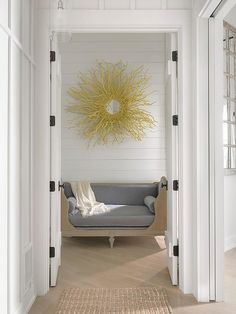 Diagonal gray wash wood floors lead to a foyer adorned with a French daybed finished with a gray velvet cushion and gray velvet bolster pillows while positioned under a gold sunburst mirror mounted on a shiplap wall.