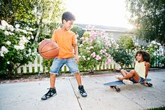 Stock Photo : Mixed Race girl on skateboard watching brother dribbling basketball