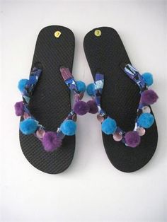 Decorated flip flops . Black flip flops decorated with a blue black white ethnic tribal prinbt,   Finished off with blue and purple pom poms and lavender shell trims.