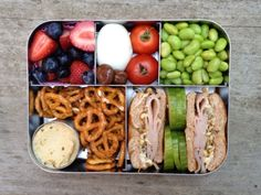 Turkey and sprout sandwich on a whole wheat mini bagel, cucumber slices, salted edamame, pretzels and hummus, cherry tomatoes, hard-boiled egg, blueberries and strawberries, and a few chocolate-covered cherries for dessert.