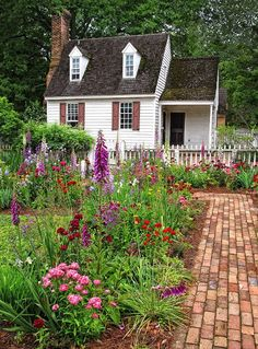 Pretty English garden leading to an adorable cottage.