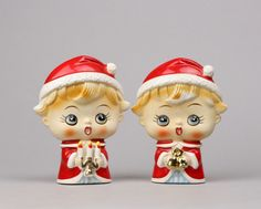 My Vesties Wish List Item These two choir members make me laugh with their big heads and narrow profiles. They are 5.5 tall, 4.25 at their widest points and a mere 2 deep. One is holding bells and the other lit candles and both are wearing Santa caps and red and white cloaks.