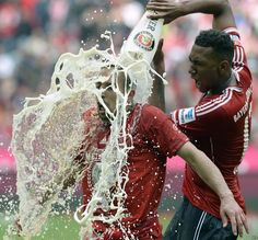Bayern Munich's defender Jerome Boateng (R) pours beer on Bayern Munich's French midfielder Franck Ribery while celebrating their champion title, after winning 3:0 the German first division Bundesliga football match between Bayern Munich and FC Augsburg in Munich, southern Germany, May 11, 2013.