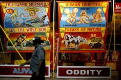 A man walks past carnival signs after sunset at the Oklahoma State Fair in Oklahoma City, Wednesday, September 19, 2012. Photo by Bryan Terry, The Oklahoman