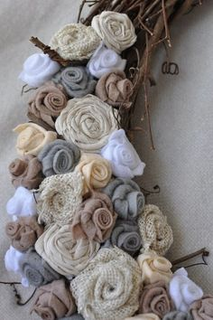 Cool rolled flower wreath. Love the different materials and textures! This would be fun to make out of all those wedding scrap materials- bm dresses- veil- hem from wedding dress- leftover  reception runners
