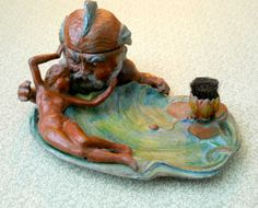 Neptune admired by a nude lady. This inkwell feature a pen wipe coming out of the lily blossom. The inkwell is in the top of Neptune's head that hinges open.( So very art nouveau). _Judith Walker's Collection