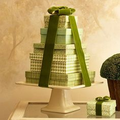 Gifts on a Pedestal  Cake plates seldom get used steadily so put one to work in your Christmas display. Lidded boxes wrapped in coordinating scrapbook papers and stacked from largest to smallest make their grand stand on a square cake pedestal. Pretty velvet ribbon pulls it all together.