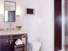 White square tiles complement a walnut vanity and accents in this clean-lined modern bathroom.