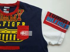"""American flag andTommy Hilfiger Shout out tshirt with a front pocket. Length: 28"""". Shows some wear and color fading due to its age. But since this is 90's t-shirt and it is in good condition. White, yellow, red, blue. 