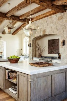 Lanterns, rustic wood island, stone hearth wall, and beamed ceilings in a kitchen of a French Country Provençal Gustavian Style Home. #kitchen #frenchcountry #provencal #provence #rustic #nordicfrench #gustavian