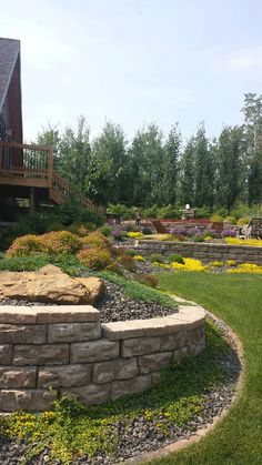 Using a hillside to your advantage by creating a 3-tiered rock wall landscape with a patio. Lakeside Cottages and Country Homes | Creative Landscape & Design
