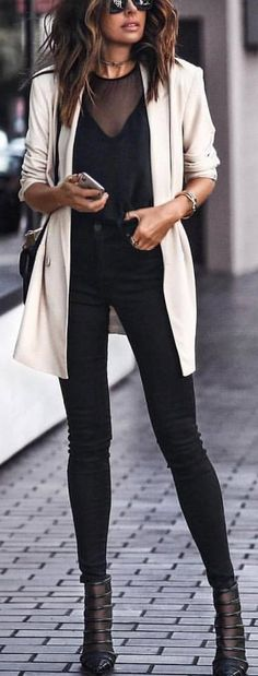 black top, skinny pants and boots with white jacket