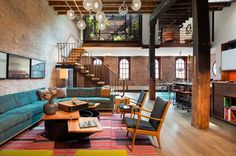The large open living space on the first floor of the apartment uses some of the wood beams and exposed brick left over from the building's history. However, it also adds gorgeous hardwood floors and plenty of colorful accents, including a stunning teal sofa and creative modular coffee table.