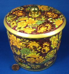 This is an English tea tin or tea canister with a design of a brown and gold floral transfer with green touches and gold over design. The tin has gold trim, a gold ball finial on the friction fir lid.