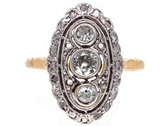An Art Deco oval shaped ring set with three diamonds in a downward line and surrounded by small diamonds. The top is platinum and the shank is 18ct gold. It was most likely made in Germany or Austria circa 1920.