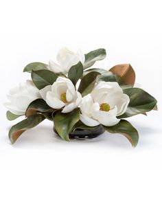 """{$tab:description} Add the perfect decorativetouch Our signature classic white magnolianot only looks as real as its live counterpart but also feels as real.In addition,the softly curled leaves withrich green tops and fuzzy rust undersidesensure naturalrealism. This glorious silk magnolia centerpiece is arranged in a low glass bowl with black beach pebbles in our crystal clear acrylic water.{$tab:DETAILS}  10"""" Height x 20"""" Width Heavy Glass Bowl - 3.5..."""