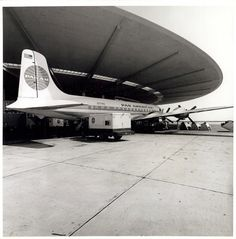 "Pan American World Airways Douglas DC-7B ""Clipper Evening Star"" shelters under the vast roof of the Pan Am Worldport at Terminal 3 of what was then Idlewild Airport and now known as JFK (ca. 1961)."