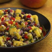 Roasted Corn, Black Bean & Mango Salad  This simple, fresh-tasting salad adds delicious variety to grilled foods, such as salmon, halibut, chicken, or pork. Browning the corn in a skillet gives it a nutty, caramelized flavor that contrasts with the sweetness of the mango.