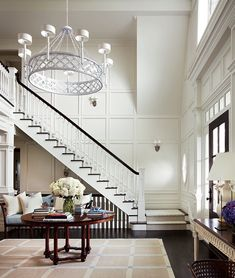 see the sofa under the stairs in this foyer - Rather than feeling imposing, this large, beautiful foyer feels warm and welcoming