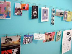 run picture hanging wire across room with hanging clips to display work that you want to see, but not necessarily frame.  Easy to curate!