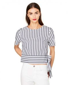 Short blouse with round neck and short sleeves. At the front this piece is in stretch poplin cotton, while the back panel is in 100% cotton jersey. It features a band that's attached to the bottom, tied with a knot on one side. Boxy fit.