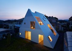 A metal roof completely surrounds this house by Japanese studio Suppose Design Office, sheltering terraces and a garden so that residents can use these spaces all year round.