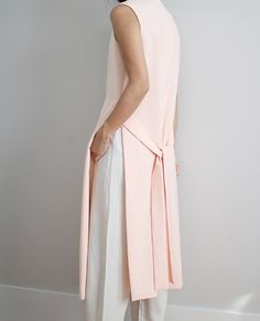 Pink sleeveless coat/waistcoat and white linen trousers.