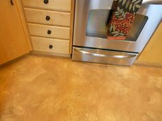 Warm tones of decoupage floor match maple wood in kitchen