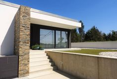 Von außen zeigt sich der Flachbau modern und schlicht und überzeugt mit Highlights wie einer vorgezogenen Steinwand und einem über die Terrasse hinweg reichenden Dach.