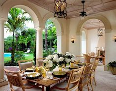 Palm Beach FL loggia by interior designer David Kleinberg features a simple table flanked by rattan chairs with oyster cushions.