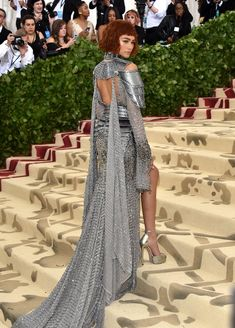 Is that Joan of Arc or Zendaya? It's Zendaya paying homage to the fearless crusader at the Met Gala. The 21-year-old actress and singer, who was dressed by longtime stylist Law Roach, arrived in a spectacular silver Versace dress that looked like a knight's armor with the metal shoulder pads and chain details. She paired it with matching Jimmy Choo heels and Tiffany & Co. jewelry. When she turned around, you could see the back peephole and her gorgeous chain-link train, which looked heavy to…