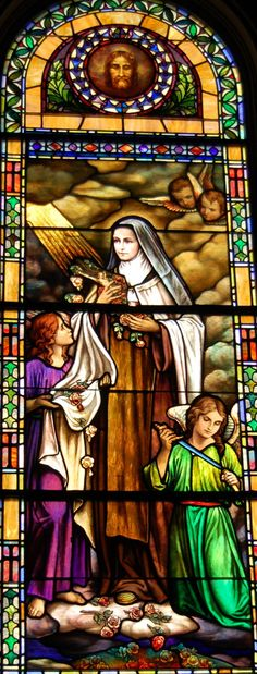 "October 1st is the Feast of St. Therese of the Child Jesus of the Holy Face. Also known as St. Therese of Lisieux and the Little Flower. The ""Shower of Roses"" window was installed before her beatification in 1923 in anticipation of sainthood. One angel is sheathing his sword, now that the battle is over. St. Theresa was a Carmelite Nun and is the Patroness of the Carmelite order along with St. Teresa of Avila and the Holy Mother. Chapel of the Holy Spirit at Philadelphia Carmel."