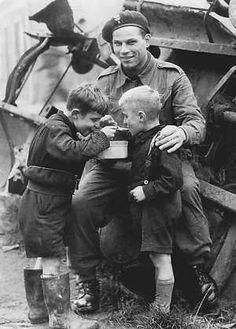 Soldado polaco soldado del Ejército Libre comparte su comida con dos niños holandeses durante la liberación de los Países Bajos, 1945.