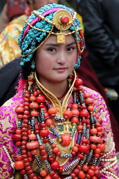 A Khampa Tibetan girl in a traditional ceremonial costume from Palyul county. She wears the traditional women's headdress in Palyul with many strands of turquoise, and a gold necklace across her forehead, nine necklaces of coral and contemporary dzi, and coral and dzi beads set gold rings on six fingers. The costume and ornaments are the belongings of her family, and contain much of the family's wealth and savings.