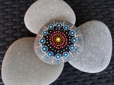 Hand painted Mandala Stone. A special item for yourself, unique gift to a friend, eye-catching decoration, talisman, treasure for your kids,...  The stone has been hand collected on a pebble beach, carefully cleaned and painted with acrylic colours. A special varnish protects the stone from sunlight and rain. This means it fully weatherproof can be used for outdoor decoration as well.  Mandalas represent the universe, cosmos and wisdom. They are often used as an aid to meditation and inner…
