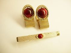 """Cranberry Round MoonGlow Cufflinks Vintage Wrap Mesh Tie Clip Gold Filled Signed by Swank business wedding anniversary. This is set of Vintage Cranberry Round Moon Glow Wrap Mesh Cufflinks and Tie Bar Signed by Swank. The moonglow stones together with wrap mesh design make these cufflinks a have to own pair. Add in the tie bar and this is a perfect combination for a dressy occasion. The cufflinks measure 2 3/8"""" unrolled and 1 3/8"""" when rolled and closed. The face is 3/4"""" wide. The tie bar is…"""