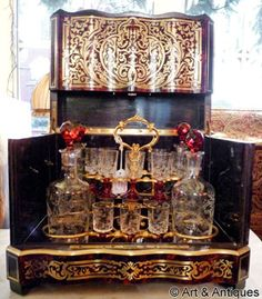 Cave à liqueur en marqueterie Boulle Verrerie cristal ciselé et piètement rouge