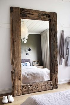 Large barnwood mirror.Behind two bedside tables.