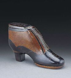 "A treen snuff box  In the form of a shoe, double-lidded, the two-colour wood with applied pique decoration and dated ""1877"