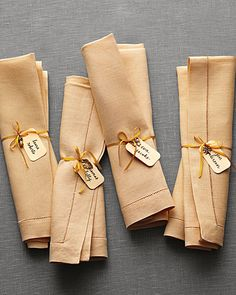 Charming Napkins    Instead of place cards, opt for this unique idea: String metal trinkets and hand-punched name tags onto ribbons, then tie them around napkins to be laid at each spot. After dinner, guests can wear them as bracelets.