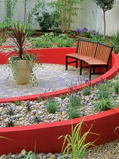 Curving around a bench, this dynamic raised bed adds color and momentum to a paved circular terrace.  A wonderful garden space.