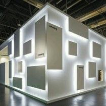 Exhibition Ideas - Comprised of little more than white laminate dotted with various square panels, Ansorg GmbH's hidden light fixtures beneath simple panels create a striking piece of shadow play! Exhibition Stand Design, Exhibition Stall, Exhibition Display, Exhibition Poster, Design Stand, Display Design, Wall Design, Banner Design, Pop Display